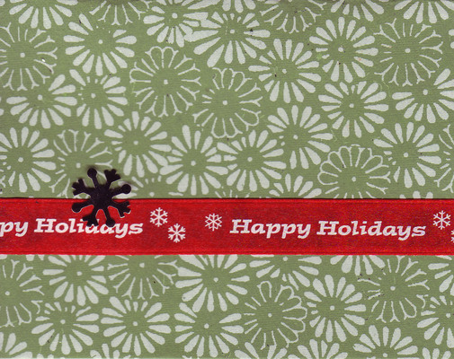 072 A red 'Happy holidays' ribbon attached to a richly textured green paper with a white floral print by a snowflake brad