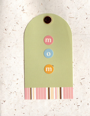 015 - 'Mom' on a tag attached by a brad to an ivory flocked paper
